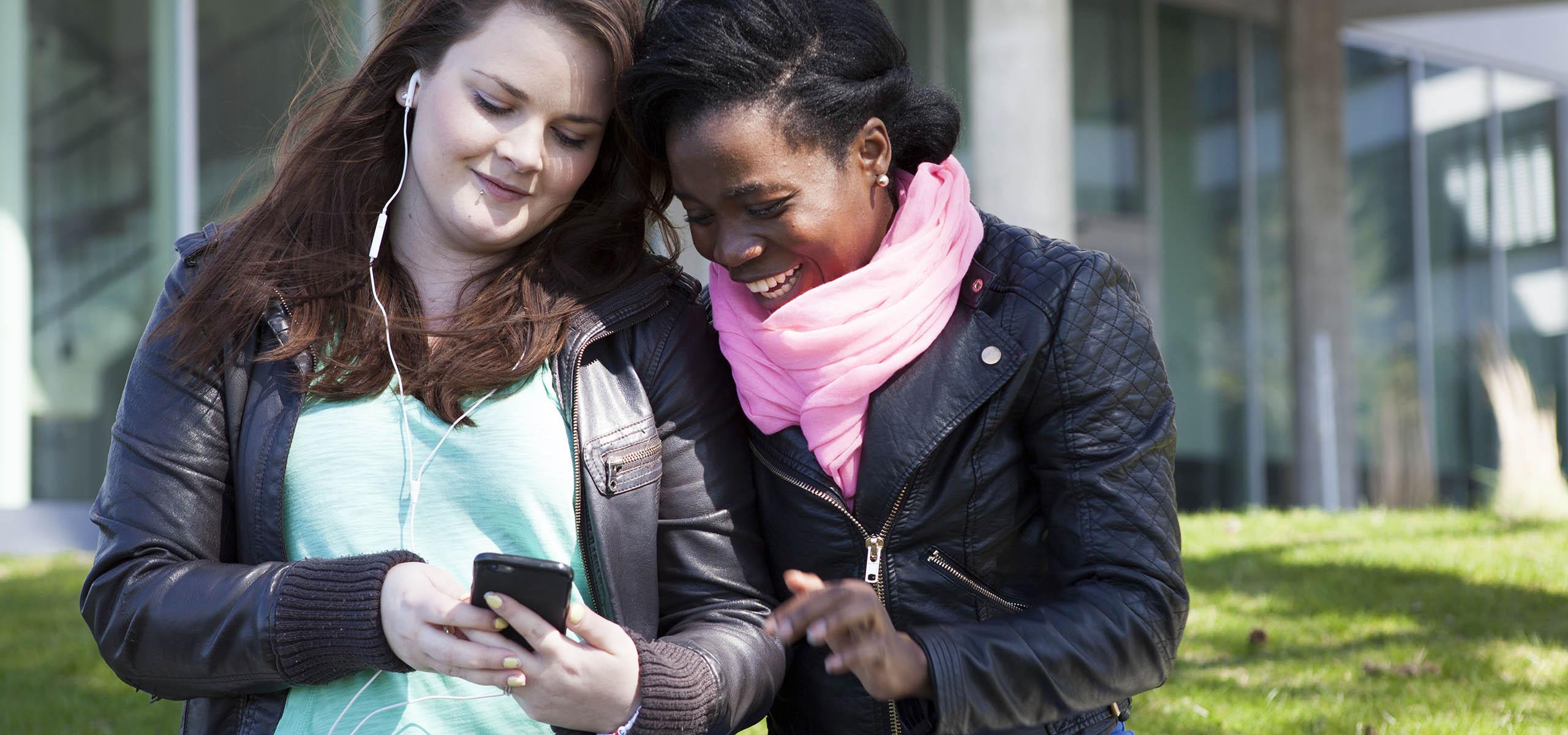 Två kvinnliga studenter tittar ner i en telefon