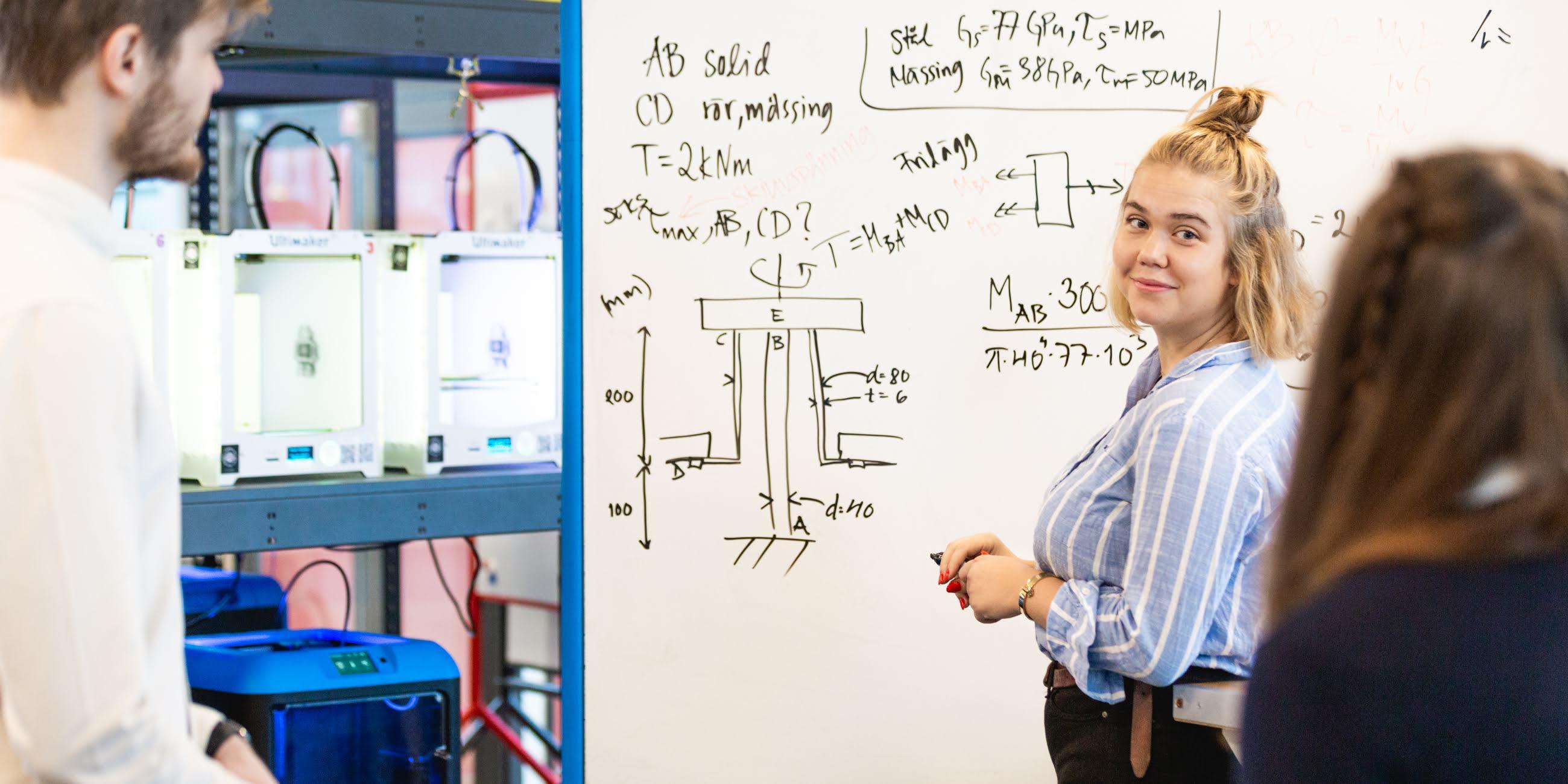 Fotografi på tjej vid whiteboard som kollar tillbaka på två andra studenter
