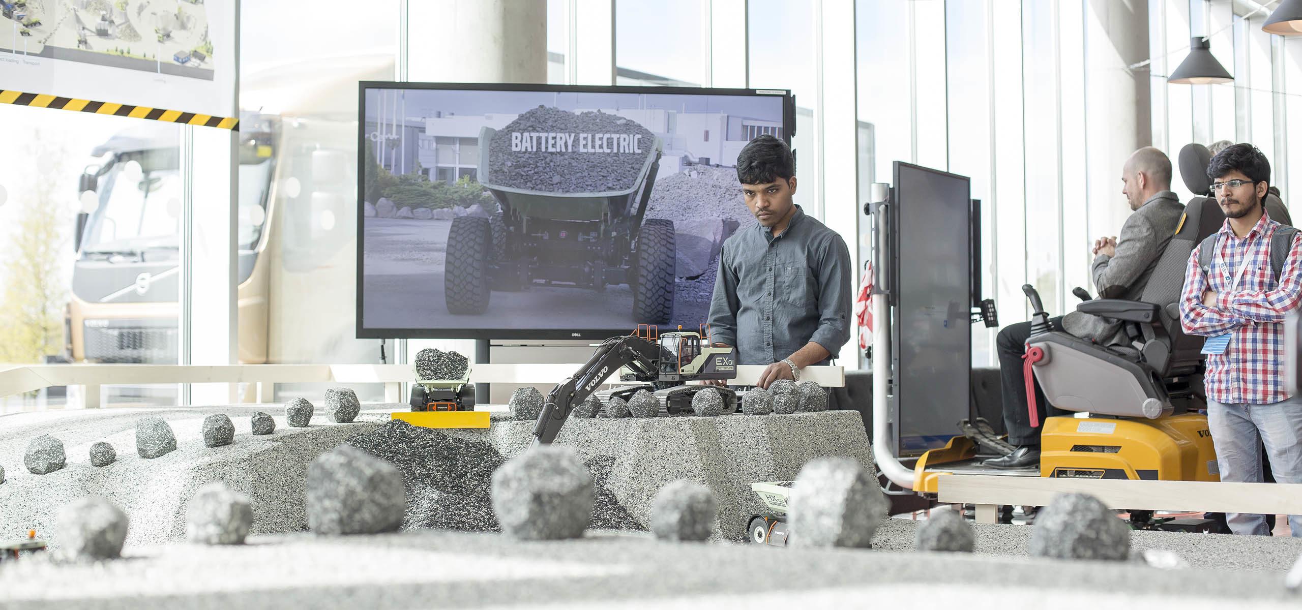 Fotografi på student som styr en radiostyrd grävmaskin, en annan student tittar på