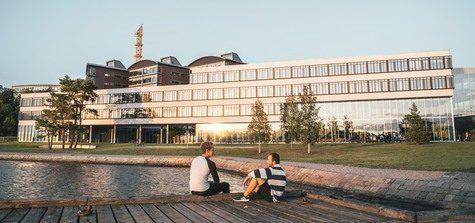 Fotografi med två studenter som sitter på badbryggan framför Campus Gräsvik