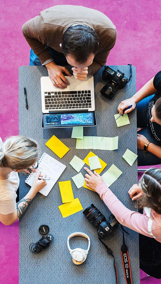 Foto på 4 studenter som jobbar i projekt med post-it lappar