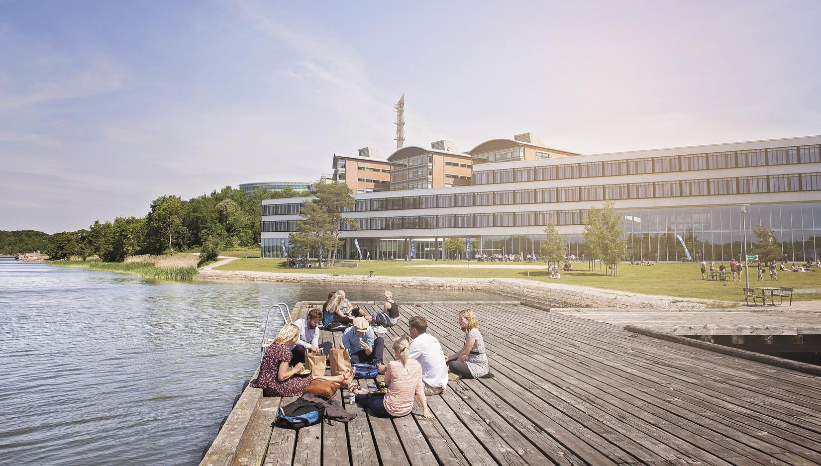 Foto på studenter i grupp som sitter i solskenet på badbryggan utanför Campus Gräsvik