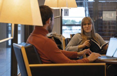 Foto på två studenter som sitter och studerar på biblioteket
