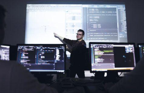 Foto på studenter framför stora skärmar i datorsäkerhetslabb