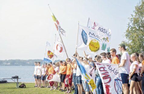 Foto på studenter med fanor under introduktionsveckan, nere vid vattnet, Campus Gräsvik