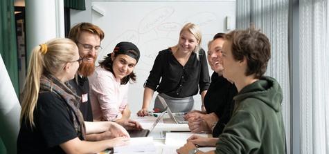 Foto på sju studenter som jobbar i ett grupparbete