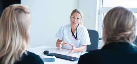 Kvinna med sjukvårdsuniform samtalar med två personer