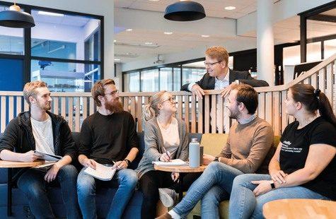 Foto på studenter i arbetsgrupp som samtalar med rektor