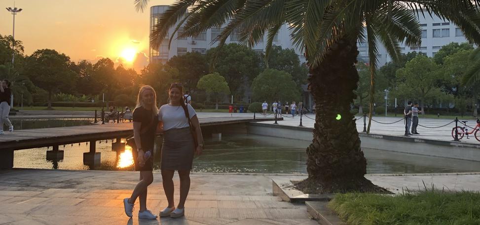 Foto på två tjejer i solnedgången vid en palm