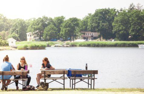 Foto på studenter som sitter och fikar på bänkar nere vid vattnet, Campus Gräsvik