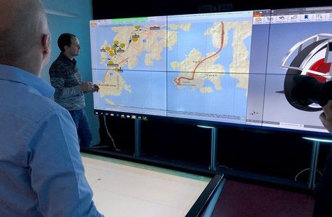 Foto på forskare vid stora datorskärmar med kartor