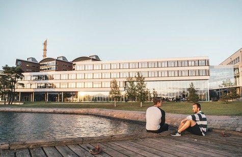 Foto på två studenter som sitter på badbryggan utanför Campus Gräsvik