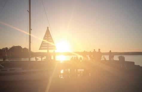 Foto på studenter vid bryggen i solnedgången