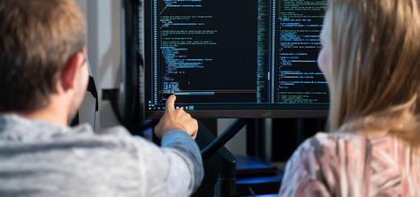Bild på kille som pekar på kod på skärm