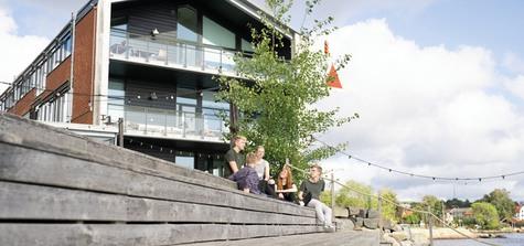 Grupp med studenter sitter på bryggan utanför Campus Karlshamn