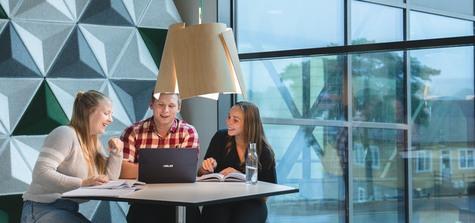 Tre studenter står vid ett bord med laptop