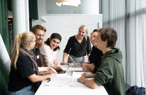 Personer som sitter runt ett bord och diskuterar