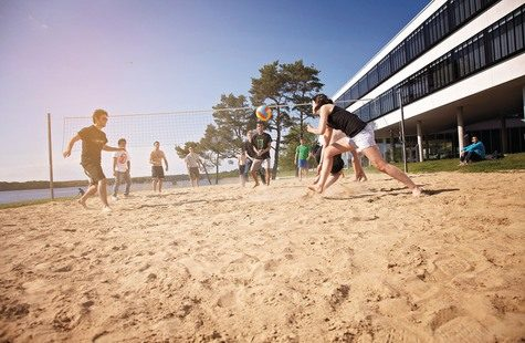 Students plays volleyball outside campus