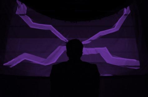 Foto på person i siluett framför stor skärm