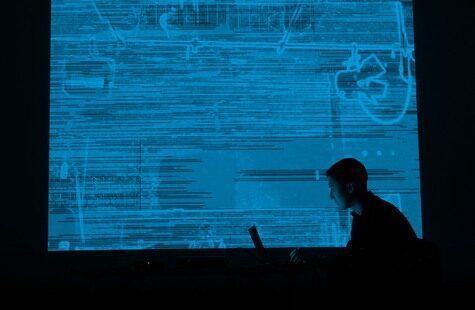 Foto på student som arbetar framför stor skärm med mönster