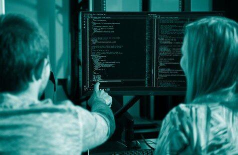 Foto på två studenter framför skärm med kod