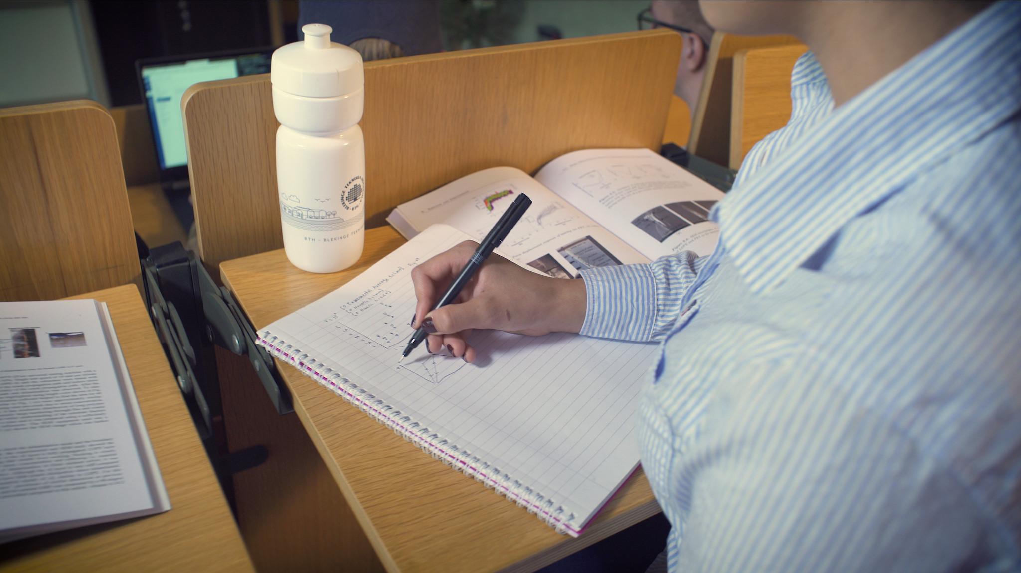 Kvinna sitter med penna och papper på en föreläsning